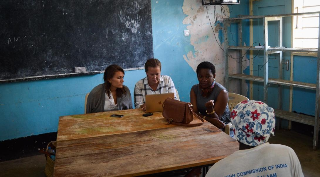 Students offer advice to a local woman during their Human Rights internships in Tanzania.